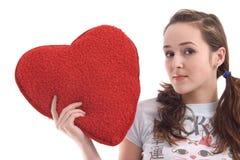 Muchacha con el corazón rojo grande de la felpa Foto de archivo libre de regalías