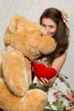 Muchacha con el corazón y el oso rellenos foto de archivo