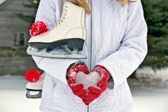 Muchacha con el corazón y los patines del hielo Foto de archivo libre de regalías