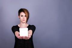 Muchacha con el corte de pelo corto que sostiene la caja blanca Foto de archivo libre de regalías