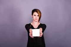 Muchacha con el corte de pelo corto que sostiene la caja blanca Imagen de archivo libre de regalías