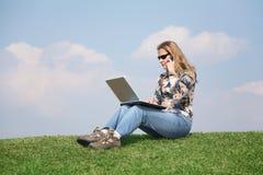 Muchacha con el cuaderno en hierba imagen de archivo libre de regalías
