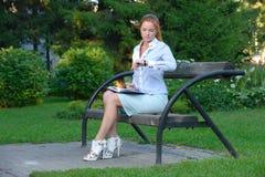Muchacha con el cuaderno que se sienta en el banco Imagenes de archivo