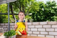 Muchacha con el cuchillo grande en la tabla con las verduras Imagen de archivo libre de regalías