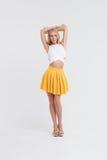 Muchacha con el cuerpo perfecto en falda amarilla en el fondo blanco Fotos de archivo