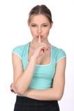 Muchacha con el dedo en sus labios Cierre para arriba Fondo blanco Imagen de archivo