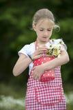 Muchacha con el delantal y el ramo de margaritas al aire libre Imagen de archivo libre de regalías