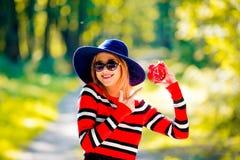 Muchacha con el despertador rojo en un parque foto de archivo