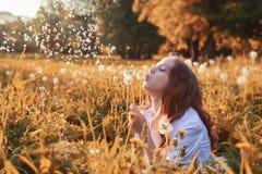 Muchacha con el dundelion en parque del otoño Fotografía de archivo