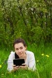 Muchacha con el ebook que miente en la hierba Fotos de archivo libres de regalías