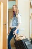 Muchacha con el equipaje que sale de su hogar Imagen de archivo