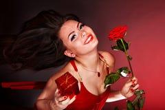 Muchacha con el funcionamiento del rectángulo de la rosa y de regalo de la flor. Fotografía de archivo libre de regalías