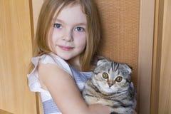 Muchacha con el gatito gris Fotos de archivo