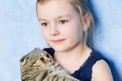 Muchacha con el gatito gris Imagenes de archivo