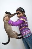 Muchacha con el gato siamés Fotografía de archivo