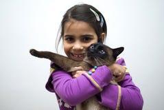 Muchacha con el gato siamés Fotos de archivo