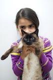 Muchacha con el gato siamés Foto de archivo