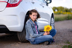 Muchacha con el girasol que la inclina detrás contra el coche Imágenes de archivo libres de regalías