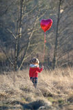 Muchacha con el globo en forma de corazón que se coloca en un campo Fotografía de archivo