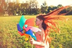 Muchacha con el juguete del molinillo de viento fotografía de archivo