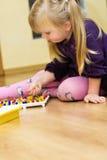 Muchacha con el juguete educativo del rompecabezas del perno Fotos de archivo libres de regalías