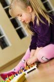 Muchacha con el juguete educativo del rompecabezas del perno Fotos de archivo
