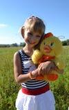 Muchacha con el juguete suave y colorido Fotos de archivo