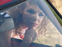 Muchacha con el lápiz labial y el espejo del coche imagen de archivo