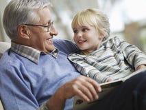 Muchacha con el libro de abuelo de la historia de la lectura Imagenes de archivo