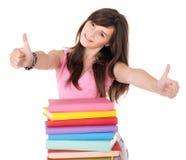 Muchacha con el libro de la pila que muestra el pulgar para arriba. Imagen de archivo libre de regalías