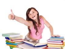 Muchacha con el libro de la pila que muestra el pulgar para arriba. Fotos de archivo libres de regalías