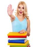 Muchacha con el libro de la pila que muestra el pulgar para arriba. Imagenes de archivo