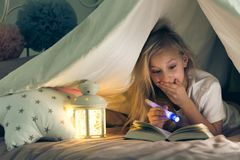 Muchacha con el libro de lectura de la linterna fotos de archivo libres de regalías
