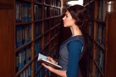 Muchacha con el libro de texto selecto del cuaderno en biblioteca Imagenes de archivo