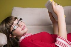 Muchacha con el libro en el sofá Imagenes de archivo