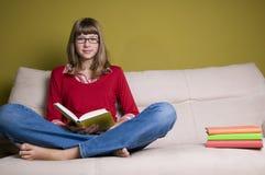 Muchacha con el libro en el sofá Fotografía de archivo