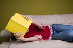 Muchacha con el libro en el sofá Imágenes de archivo libres de regalías