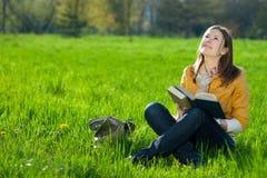 Muchacha con el libro en la hierba Fotos de archivo libres de regalías