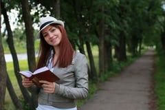 Muchacha con el libro en parque Imagenes de archivo