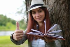 Muchacha con el libro en parque Foto de archivo