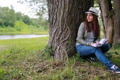 Muchacha con el libro en parque Fotos de archivo libres de regalías