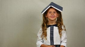 Muchacha con el libro en su sonrisa principal De nuevo a concepto de la escuela almacen de metraje de vídeo