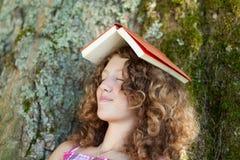 Muchacha con el libro en tomar una siesta principal en tronco de árbol Imagenes de archivo