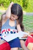 Muchacha con el libro que rasguña su cabeza en la hamaca al aire libre Fotos de archivo libres de regalías