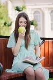 Muchacha con el libro y el aple al aire libre Fotografía de archivo