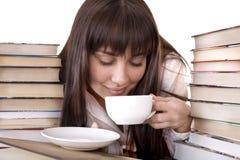 Muchacha con el libro y la taza del montón. Foto de archivo libre de regalías