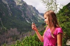 Muchacha con el móvil en las montañas Fotografía de archivo