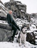 Muchacha con el Malamute del perro entre rocas en invierno Imagen de archivo libre de regalías