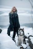 Muchacha con el Malamute del perro entre rocas en invierno Fotografía de archivo