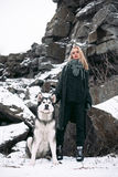 Muchacha con el Malamute del perro entre rocas en invierno Fotos de archivo libres de regalías